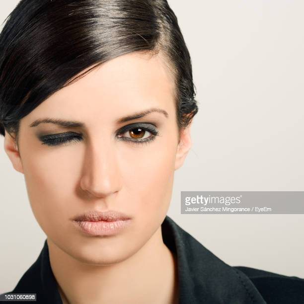 portrait of woman winking against white background - eye liner stock photos and pictures