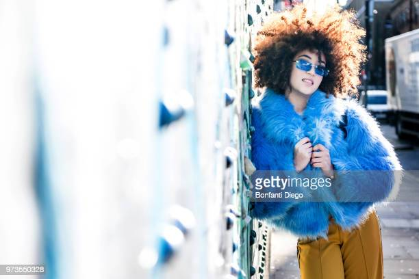 portrait of woman with afro hair wearing fur coat, leaning against wall looking at camera - fur coat stock pictures, royalty-free photos & images