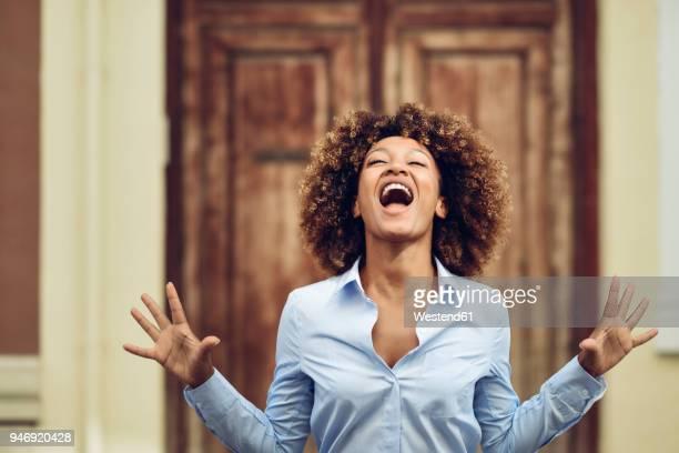 portrait of woman with afro hairstyle screaming outdoors - beugen oder biegen stock-fotos und bilder