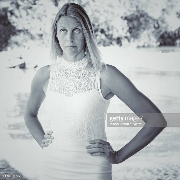 portrait of woman with arms akimbo standing in park - arms akimbo stock pictures, royalty-free photos & images