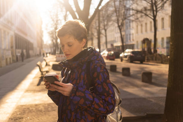 Portrait of woman with backpack and coffee to go looking at cell phone in the evening, Berlin, Germany