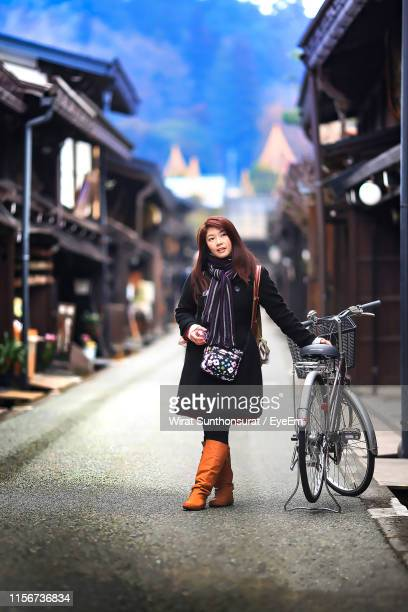 portrait of woman with bicycle standing outdoors during winter - takayama city stock pictures, royalty-free photos & images