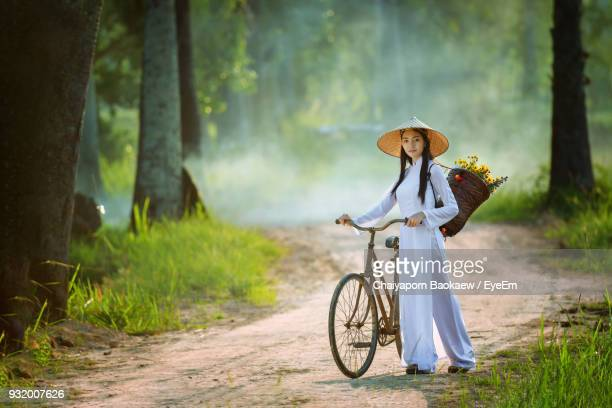 portrait of woman with bicycle wearing asian style conical hat - chapeau chinois photos et images de collection