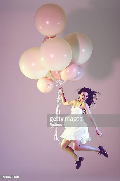 portrait of woman with big balloons - jumping stock pictures, royalty-free photos & images