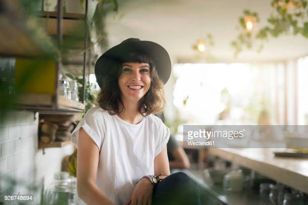 portrait of woman with black hat behind the bar in a cafe - happy merchant stock pictures, royalty-free photos & images