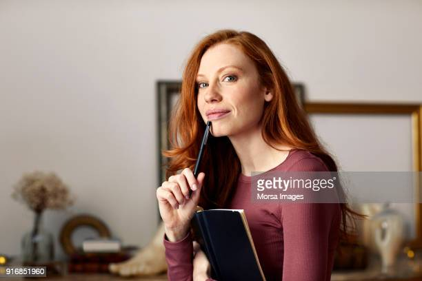 portret van een vrouw met boek en pen thuis - pen stockfoto's en -beelden