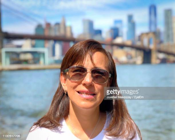 Portrait Of Woman With Brooklyn Bridge Over East River In Background