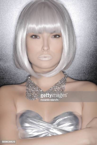 portrait of woman with brown eyes white hair and silver futuristic dress - silver dress stock pictures, royalty-free photos & images