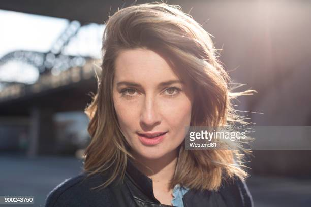 Portrait of woman with brown hair at backlight