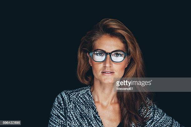 Portrait of woman with brown hair wearing glasses in front of black background