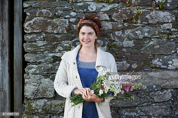Portrait of woman with bunch of wild flowers.