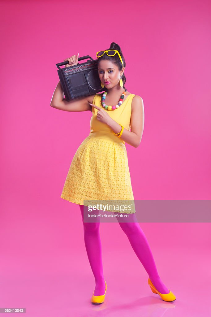 Portrait of woman with cassette player pointing : Stock Photo