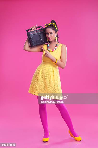 Portrait of woman with cassette player pointing