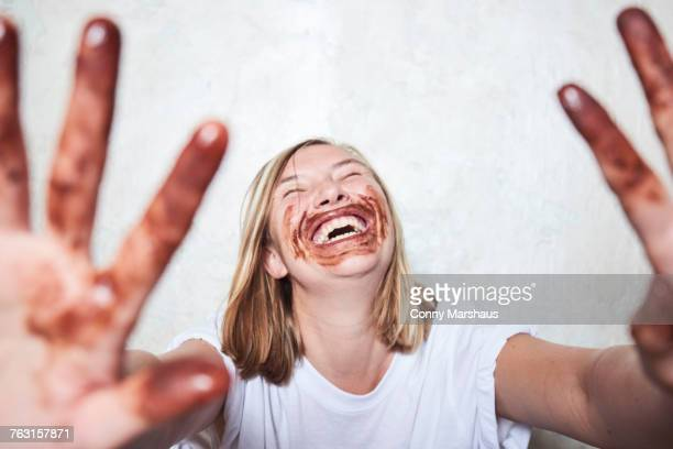 portrait of woman with chocolate on hands and around mouth, holding hands towards camera, laughing - gier stock-fotos und bilder