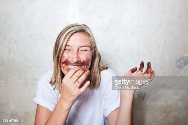 Portrait of woman with chocolate on hands and around mouth, laughing