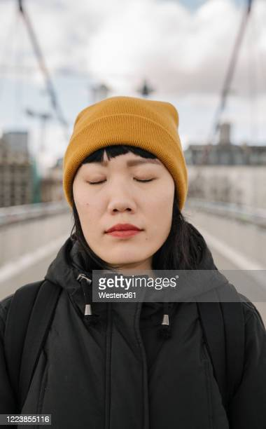 portrait of woman with closed eyes on a bridge - knit hat stock pictures, royalty-free photos & images