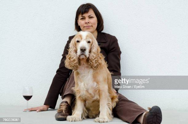 portrait of woman with cocker spaniel by wineglass sitting against wall - cocker spaniel stock photos and pictures
