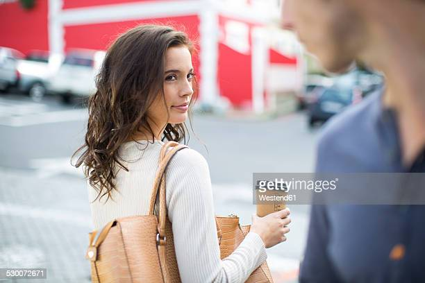 Portrait of woman with coffee to go