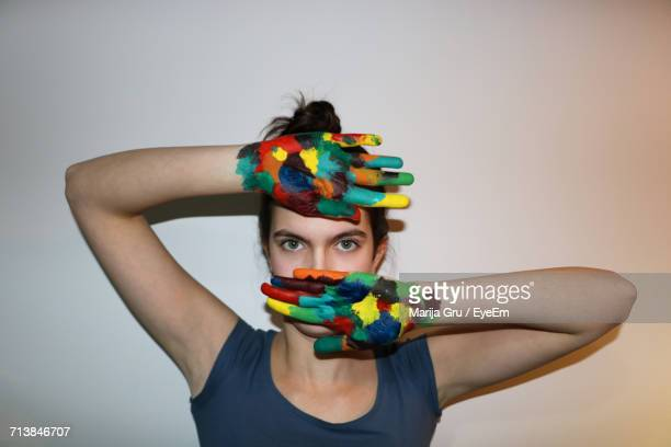 portrait of woman with colorful hand standing against wall - marija mauer stock-fotos und bilder