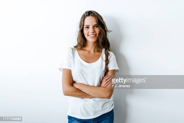 portrait of woman with crossed arms - young women stock pictures, royalty-free photos & images