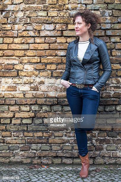 Portrait of woman with curly brown hair leaning at brick wall
