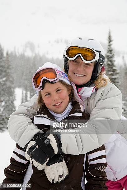 Portrait of woman with daughter (6-7) in ski-wear