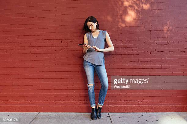 Portrait of woman with digital tablet leaning against red brick wall