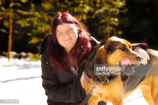 portrait of woman with dog in park during winter - coonhound stock pictures, royalty-free photos & images