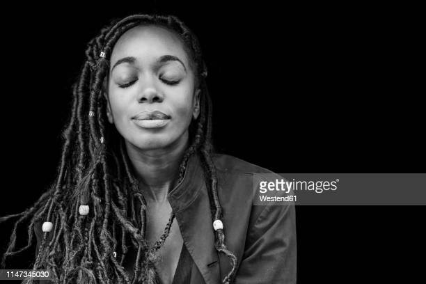 portrait of woman with dreadlocks in front of black background - black and white ストックフォトと画像