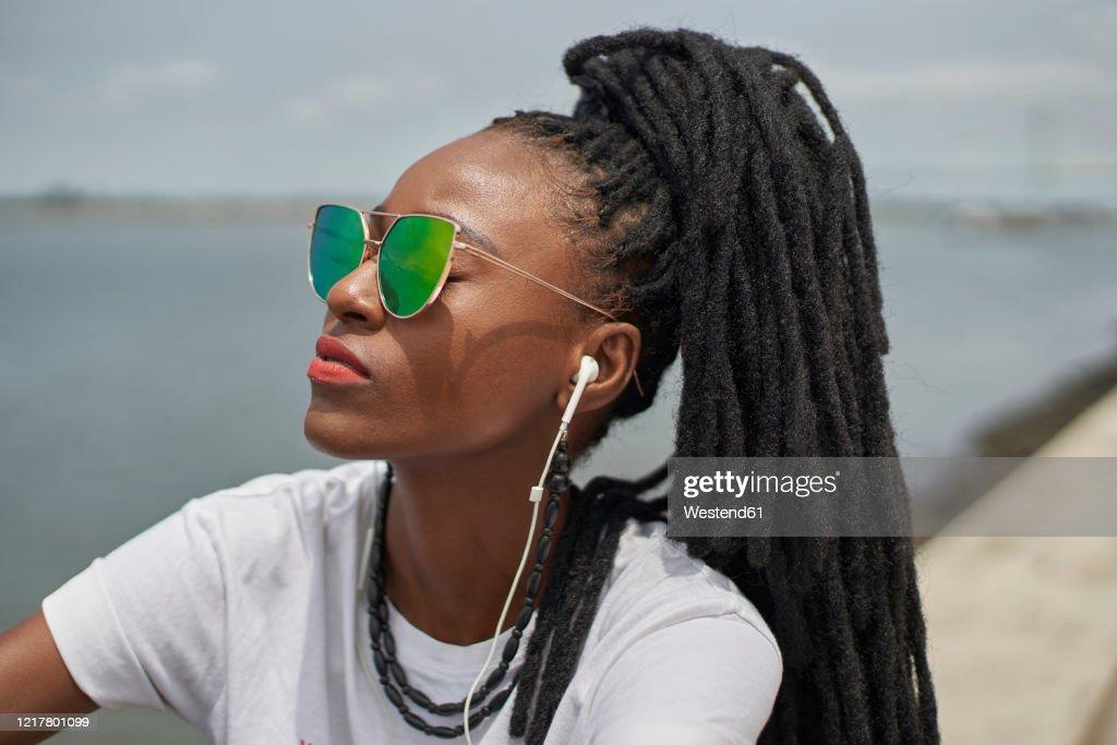 Portrait of woman with dreadlocks listening music with earphones : Stock Photo