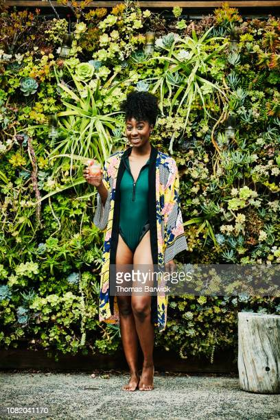 portrait of woman with drink wearing swimsuit and robe - swimwear stock pictures, royalty-free photos & images