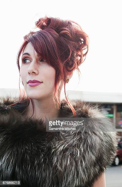Portrait of woman with dyed red hair looking away