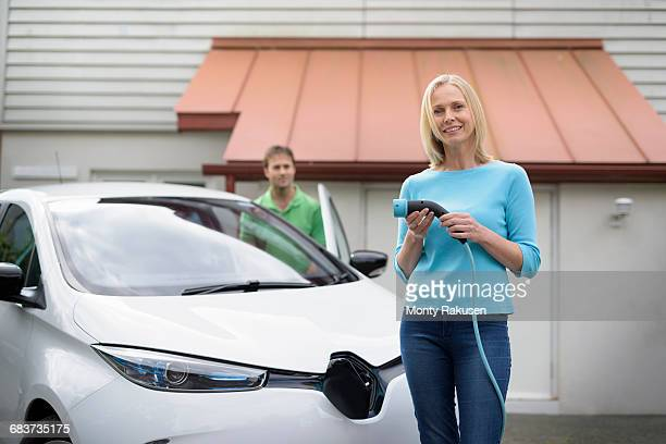 Portrait of woman with electric car, holding charging plug