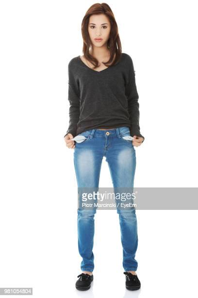 portrait of woman with empty pockets standing against white background - pocket stock pictures, royalty-free photos & images