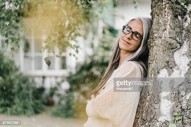 Portrait of woman with eyes closed leaning against tree trunk