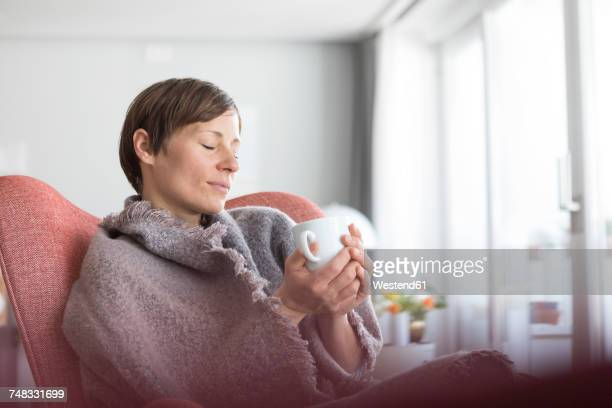 Portrait of woman with eyes closed relaxing with cup of coffee at home