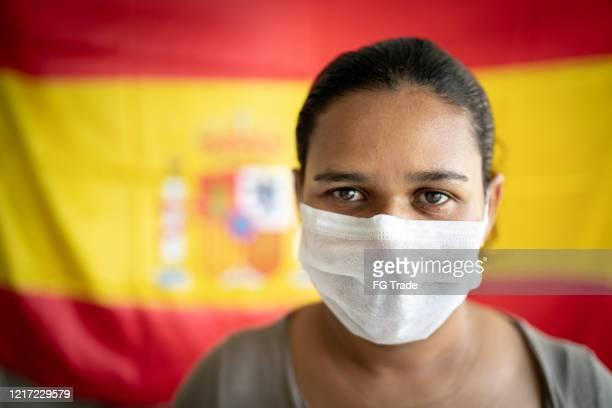 retrato de mulher com máscara facial e bandeira espanhola no fundo - espanha - fotografias e filmes do acervo