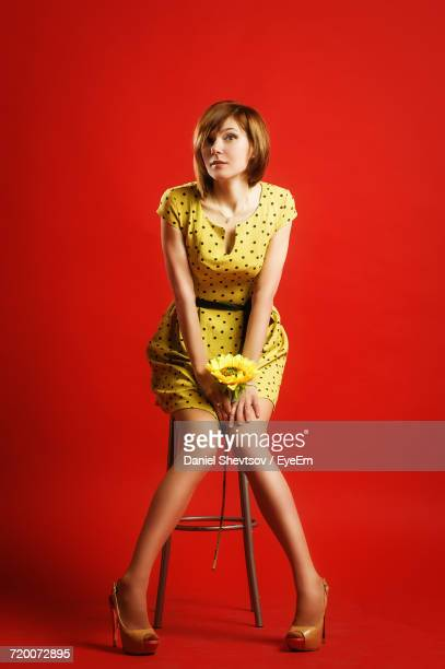 Portrait Of Woman With Flower Sitting On Stool Against Red Background
