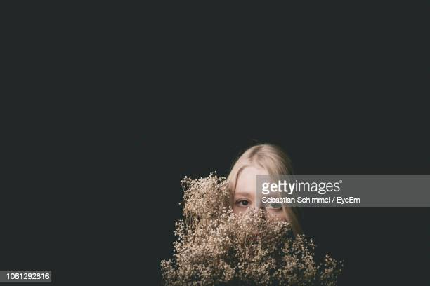 Portrait Of Woman With Flowers Against Black Background
