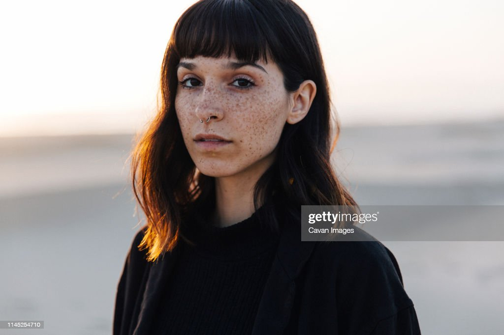 Portrait of woman with freckles standing at beach against clear sky during sunset : Stock Photo