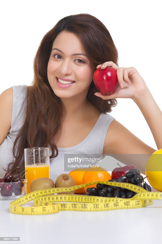Portrait of woman with fruits and measuring tape : Stock Photo