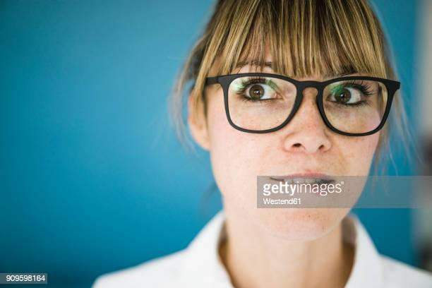 portrait of woman with glasses biting on her lip - biting lip stock pictures, royalty-free photos & images