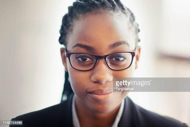 オフィスで微笑んでいる眼鏡をかけた女性の肖像 - コーンロウ ストックフォトと画像