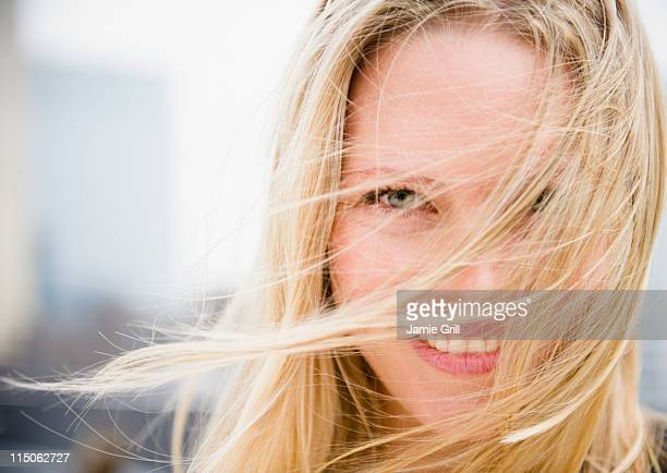 Portrait of woman with hair blowing across face