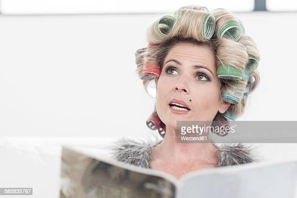 portrait of woman with hair curlers and magazine - krulspelden stockfoto's en -beelden