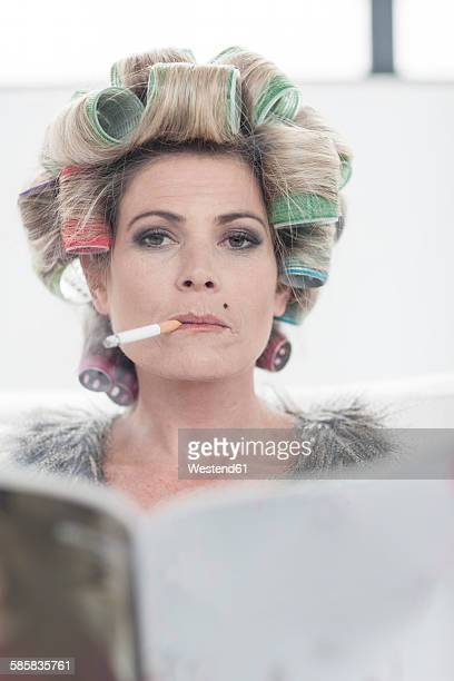 Portrait of woman with hair curlers and magazine smoking a cigarette