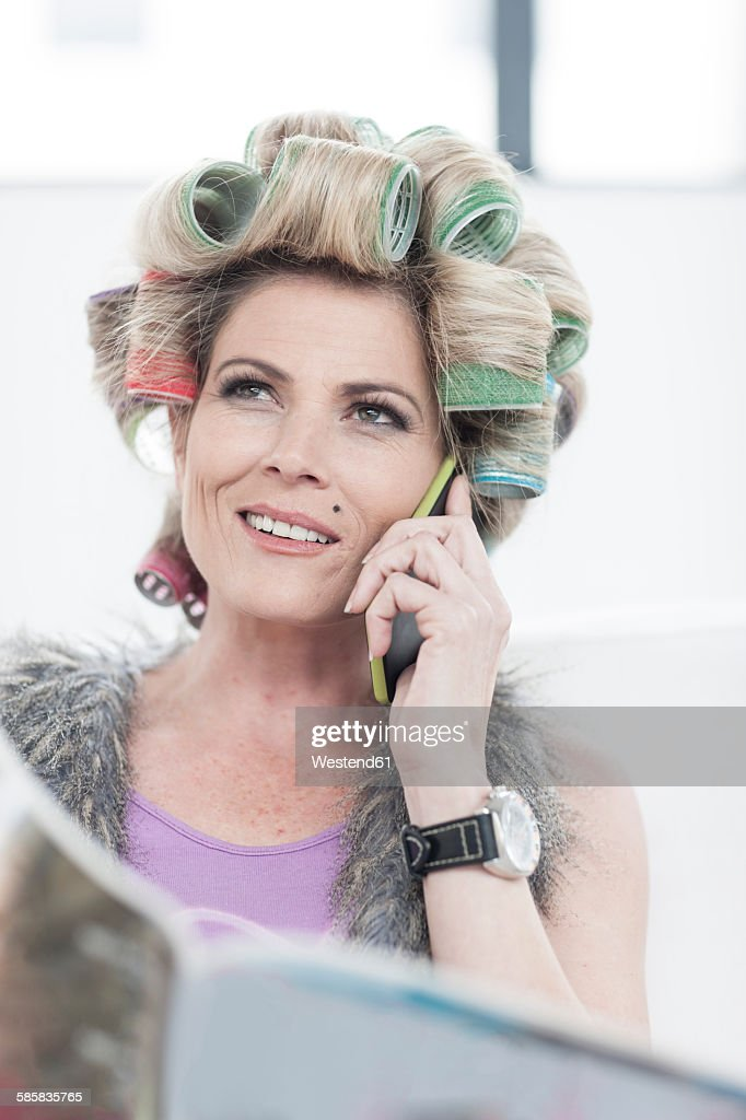 Portrait Of Woman With Hair Curlers And Magazine Talking On