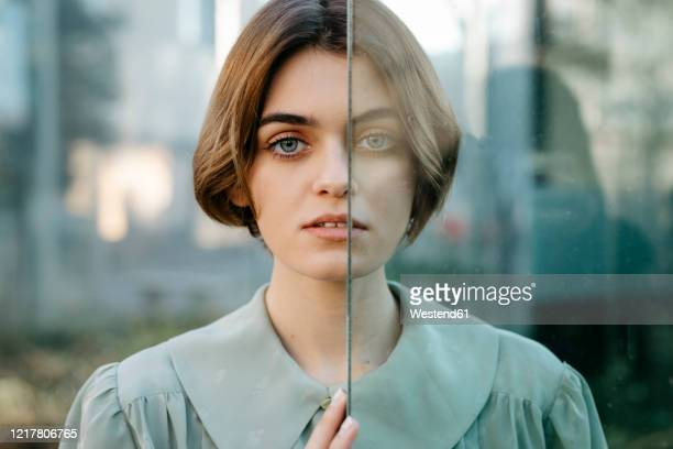 portrait of woman with half of her face behind a glass - frau bluse durchsichtig stock-fotos und bilder
