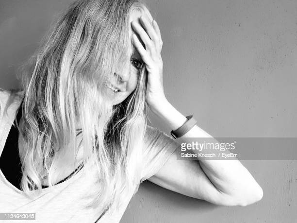 portrait of woman with hand in hair against wall - sabine kriesch stock-fotos und bilder