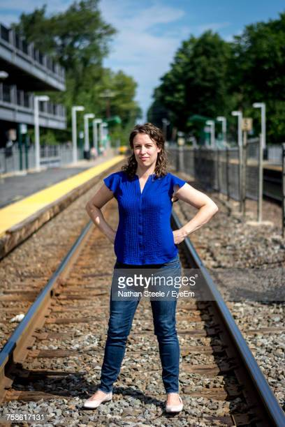 Portrait Of Woman With Hands On Hip While Standing At Railroad Track